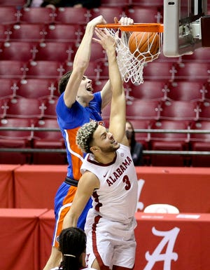 Florida forward Colin Castleton dunks with Alabama forward Alex Reese defending in Coleman Coliseum on Jan. 5.