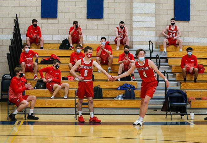 Hingham's Nick Johannes gives a hand to teammate Jack Hurley while the starting lineups were being announced at the start of their game at Plymouth North on Tuesday, Jan. 5, 2021.