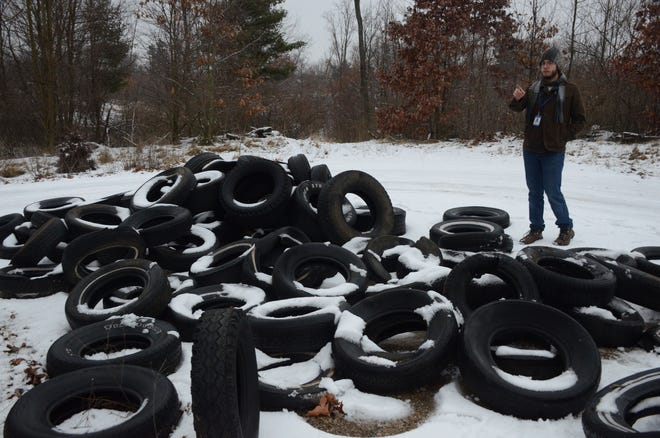 Doug Ferrall, park manager at Kimball Pines, counts the tires this week that were dumped at the park.