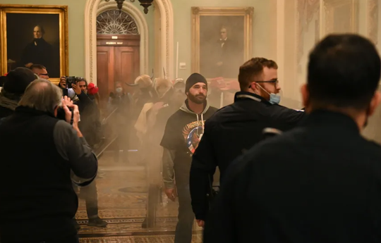 Supporters of US President Donald Trump enter the US Capitol as smoke fills the corridor on Wednesday.
