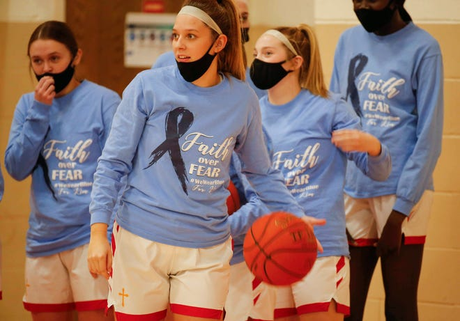 Carroll Kuemper Catholic senior Kyndal Hilgenberg leads her girls basketball team onto the court for warmups prior to tip-off against Denison-Schleswig at Carroll Kuemper Catholic High School in Carroll on Tuesday, Jan. 6, 2021. The team wears blue shirts to honor Hilgenberg's mother, Kim, who was recently diagnosed with stage 4 colon cancer.