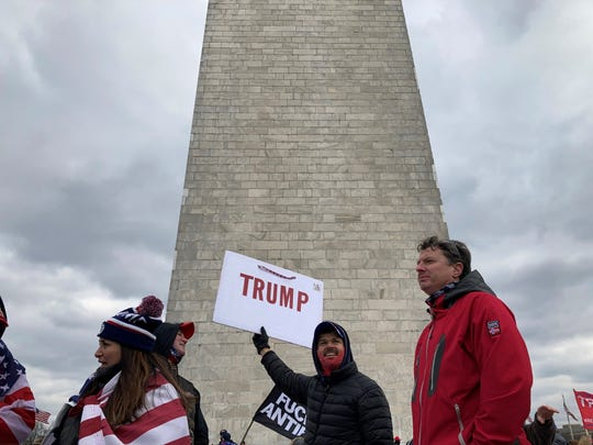 A man holding a homemade Trump sign stands at the base of the Washington Monument in Washington, D.C. on Wednesday. Trump supporters gathered in the city to protest Congress certifying the Electoral College vote in favor of President-Elect Joe Biden.