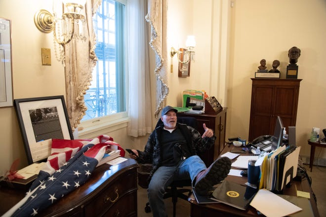 A supporter of U.S. President Donald Trump identified as Richard Barnett of Gravette sits inside the office of U.S. Speaker of the House Nancy Pelosi during the protest inside the U.S. Capitol in Washington, D.C., Jan. 6, 2021.  Demonstrators breeched security and entered the Capitol as Congress debated the a 2020 presidential election Electoral Vote Certification. (Photo by SAUL LOEB/AFP via Getty Images)
