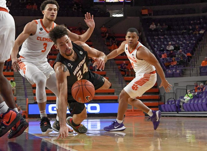 NC State guard Devon Daniels(24) loses control of the ball near Clemson sophomore guard Chase Hunter(3) and Clemson sophomore guard Nick Honor(4) during the first half Jan 5, 2021; Clemson, South Carolina, USA;  at Littlejohn Coliseum.
