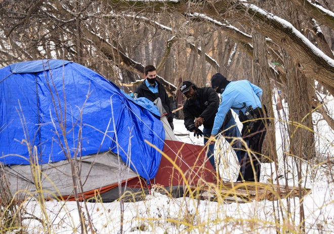 """Lansing Police Department officers respond to the scene where a homeless man was reportedly found dead inside his tent at the """"Back 40"""" homeless encampment in Lansing on Wednesday, Jan. 6, 2021."""