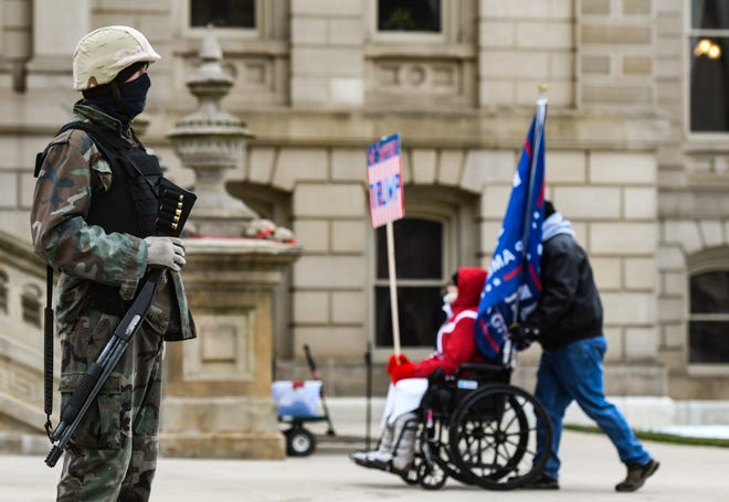 A man armed with a shotgun seen at the Michigan State Capitol Wednesday, Jan. 6, 2021, during a demonstration in support of President Donald Trump.
