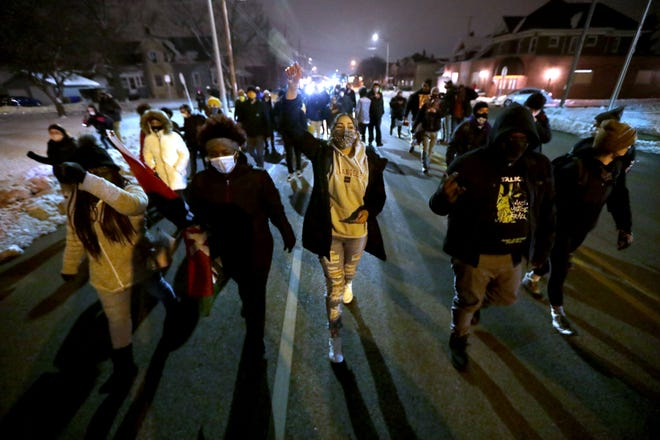 Marchers make their way down 52nd Street in Kenosha on Tuesday after an announcement from the Kenosha County district attorney that there will be no charges against officers in the shooting of Jacob Blake.