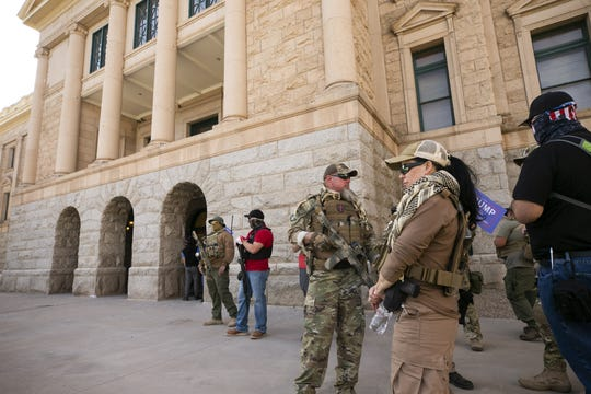 Armed individuals stand guard outside the state Capitol in Phoenix, during a pro-Trump rally, as the U.S. Congress meets in Washington, D.C., to certify the results of the presidential election, on Jan. 6, 2021.