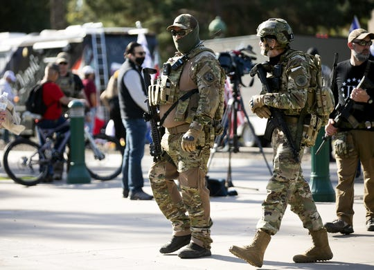 Armed men walk around the grounds of the state Capitol in Phoenix during a pro-Trump rally as the U.S. Congress meets in Washington, D.C., to certify the results of the presidential election, on Jan. 6, 2021.