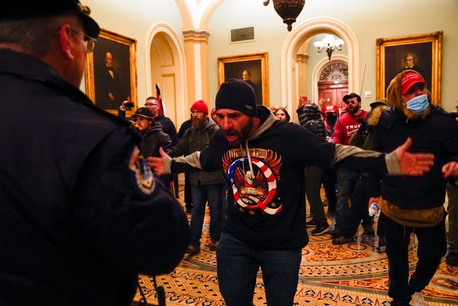 Protesters gesture to U.S. Capitol Police in the hallway outside of the Senate chamber at the Capitol in Washington, Wednesday, Jan. 6, 2021, near the Ohio Clock. (AP Photo/Manuel Balce Ceneta)