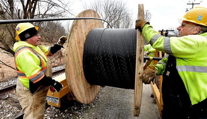 Henkels & McCoy employees Jeff Conrath, left, and Scott Stuck unspool 10,000 feet of fiber optic cable during an installation along the York County Heritage Rail Trail in Codorus Township Wednesday, Jan. 6, 2021. The York County Board of Commissioners allocated $5 million from its federal Coronavirus Aid, Relief and Economic Security (CARES) Act funding to pay for the the new broadband internet infrastructure. Bill Kalina photo