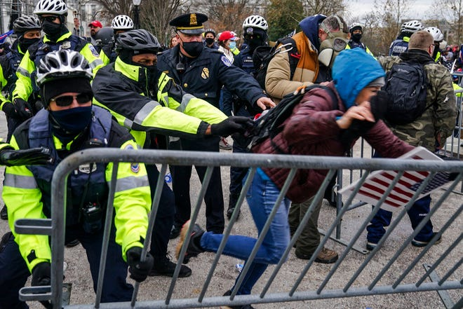 Trump supporters try to break through a police barrier, Wednesday, Jan. 6, 2021, at the Capitol in Washington. As Congress prepares to affirm President-elect Joe Biden's victory, thousands of people have gathered to show their support for President Donald Trump and his claims of election fraud.(AP Photo/John Minchillo)