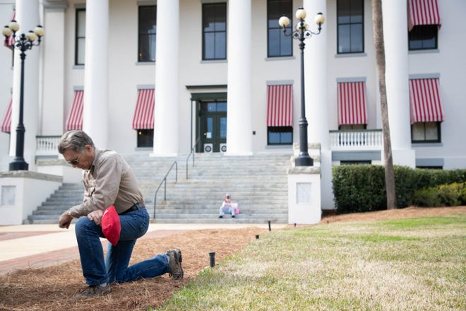 Wayne Graddick kneels in prayer in front of the Old Capitol during the Stop the Steal protest in Tallahassee Wednesday, Jan. 6, 2021.