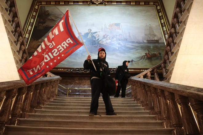 A protester holds up a Trump flag inside the United States Capitol building near the Senate House in Washington, DC