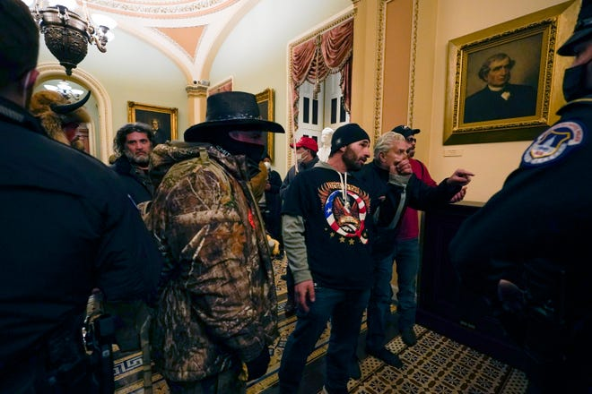 Doug Jensen (C), 41, of Des Moines and other Pro-Trump rioters confront U.S. Capitol Police officers in a hallway near the Senate chamber at the Capitol in Washington, Wednesday, Jan. 6, 2021.  Jensen was arrested by the FBI at 1 a.m. on Saturday, Jan. 9, 2021.