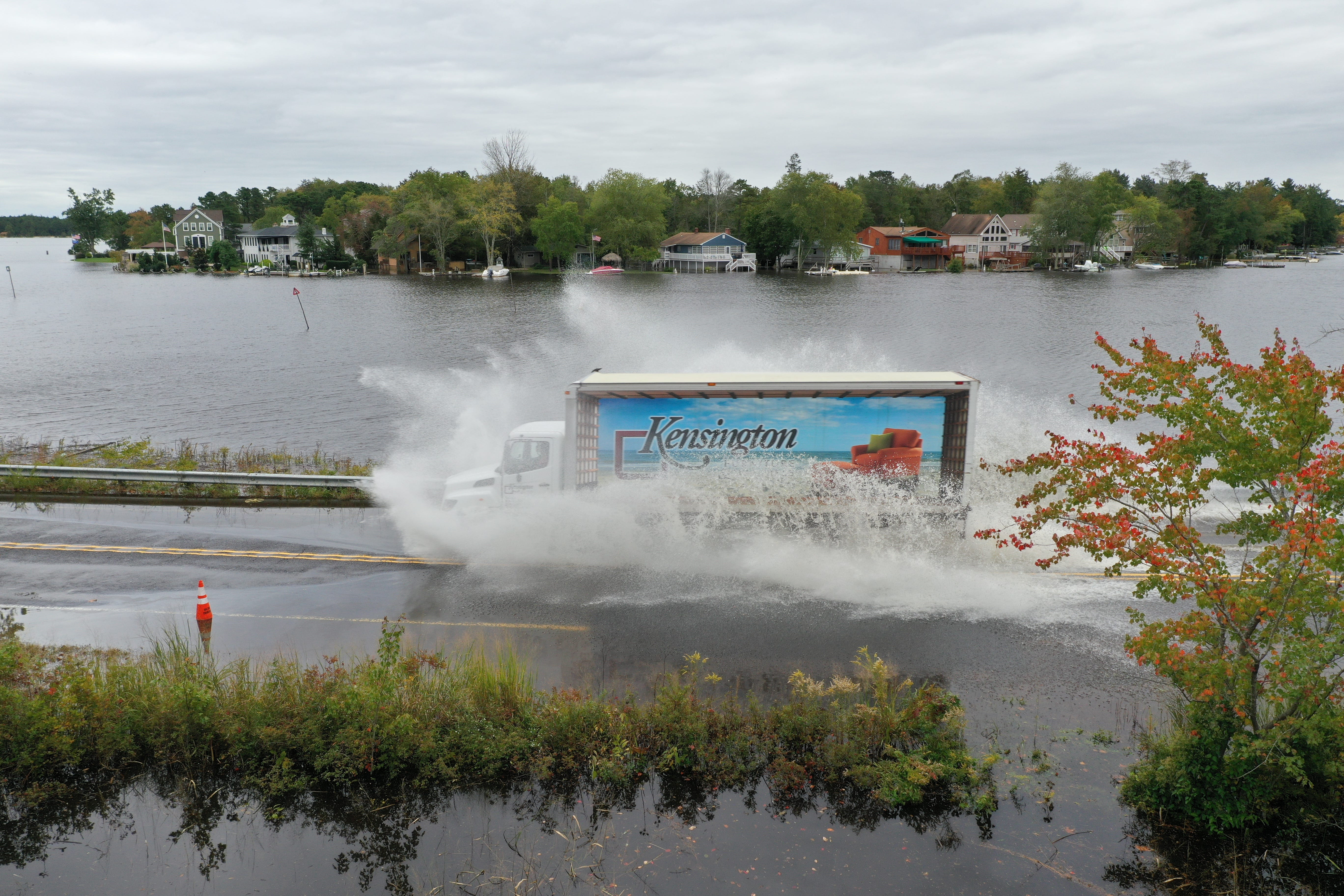 A truck navigates a flooded road during a king tide in October 2019 along the Mullica River in Southeastern New Jersey. NOAA records show coastal flooding is occurring more often as sea levels rise, especially during lunar high tides in the fall. [Photos by Life on the Edge Drones, provided by Jacques Cousteau National Estuarine Research Reserve]