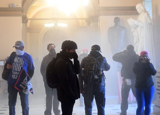 Supporters of US President Donald Trump enter the US Capitol as tear gas fills the corridor on January 6, 2021, in Washington, DC.