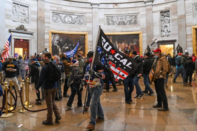 Supporters of US President Donald Trump roam under the Capitol Rotunda after invading the Capitol building on January 6, 2021, in Washington, DC. - Demonstrators breeched security and entered the Capitol as Congress debated the a 2020 presidential election Electoral Vote Certification.