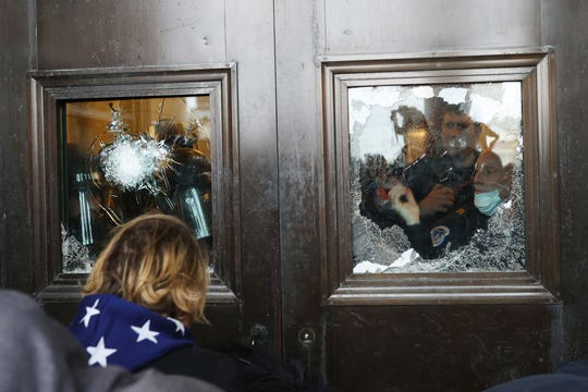 A Capitol police officer looks out of a broken window as protesters gather on the U.S. Capitol Building on January 06, 2021 in Washington, DC.