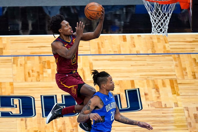 Cavaliers guard Collin Sexton, left, goes past Orlando Magic guard Markelle Fultz for a basket in the first half of the Cavs' 105-94 loss that evened their record at 4-4. Sexton scored 21 points, his eighth consecutive game over 20 points, but the short-handed Cavs are having trouble complementing Sexton's efforts on offense.  [John Raoux/Associated Press]