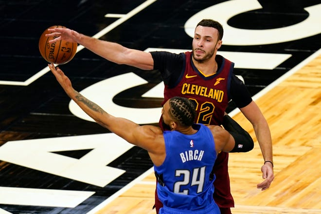 Orlando Magic center Khem Birch (24) tries to control a pass after it was deflected by Cleveland Cavaliers forward Larry Nance Jr., right, during the first half of an NBA basketball game, Wednesday, Jan. 6, 2021, in Orlando, Fla. (AP Photo/John Raoux)