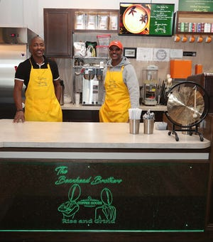 Derek Fromby, left, and Kevin Tyler stand behind the counter in their business, The Beanhead Brothers Coffee House, on Jan. 6 in Akron, Ohio.
