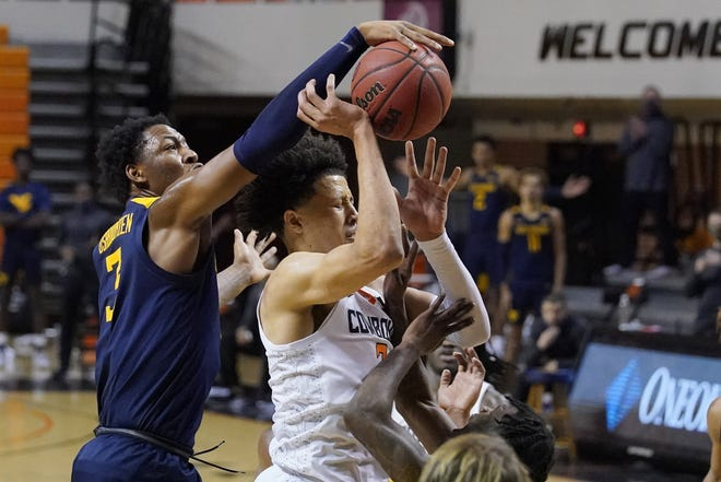 West Virginia forward Gabe Osabuohien (3) knocks the ball away as Oklahoma State guard Cade Cunningham, right, goes to the basket in the second half of an NCAA college basketball game Monday, Jan. 4, 2021, in Stillwater, Okla. (AP Photo/Sue Ogrocki)