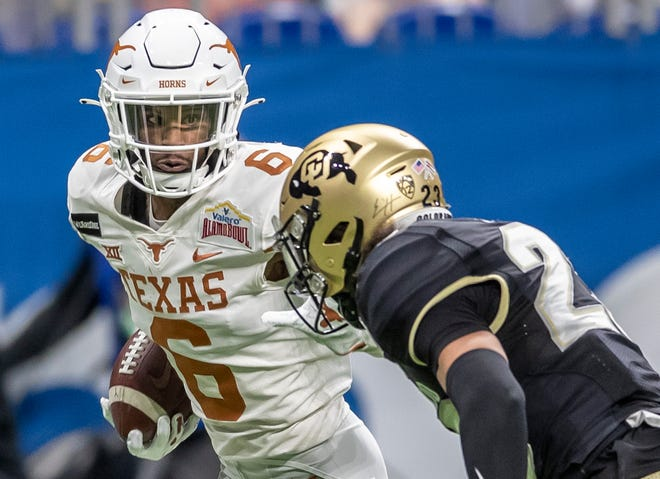 Texas receiver Joshua Moore (6) fights for yardage against Colorado safety Isaiah Lewis (23) at the Alamodome in San Antonio on Dec. 29, 2020.