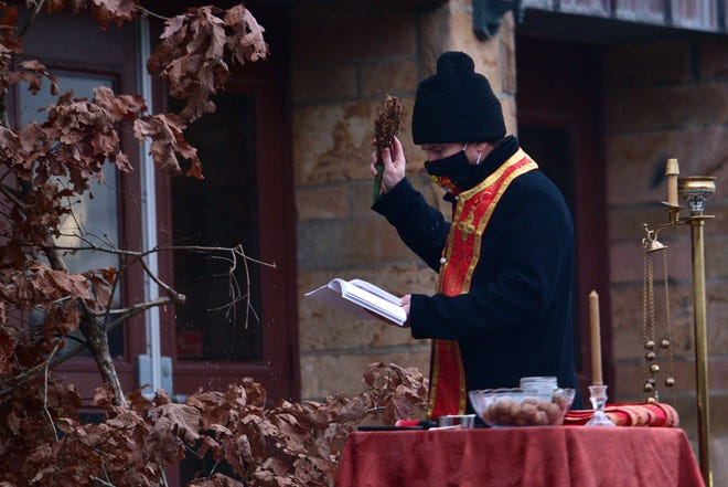 The Rev. Branislav Golic, pastor of St. Elijah Serbian Orthodox Church in Aliquippa, prays over the yule log during Christmas Eve services outside of the church Wednesday evening.