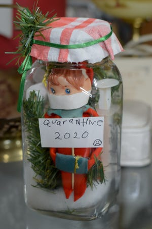 "The ""Quarantine 2020"" elf sits patiently waiting for the new year to arrive in Barnesville storefront recently."