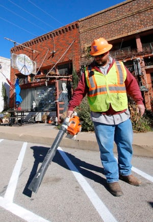 City of Brownwood Street Department employee Hobey Hoffman works with other street department workers to mark off a loading zone in front of Steves' Market and Deli at 110 E. Chandler Thursday morning.