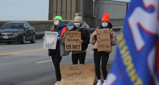 Lexa Zampanti, left, Zoe Cann and Hannah Ginsberg, all from Falmouth, lined up along the Bourne Bridge entrance to protest President Donald Trump Wednesday morning. Meanwhile, a group of his supporters circled a section of the Bourne Rotary during a rally. [Steve Heaslip/Cape Cod Times]