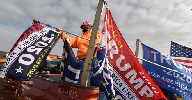 Kim Sinclair, of Plymouth, sets up her President Trump flags from the back of a pickup truck during Wednesday's rally on the Bourne Rotary. [Steve Heaslip/Cape Cod Times]
