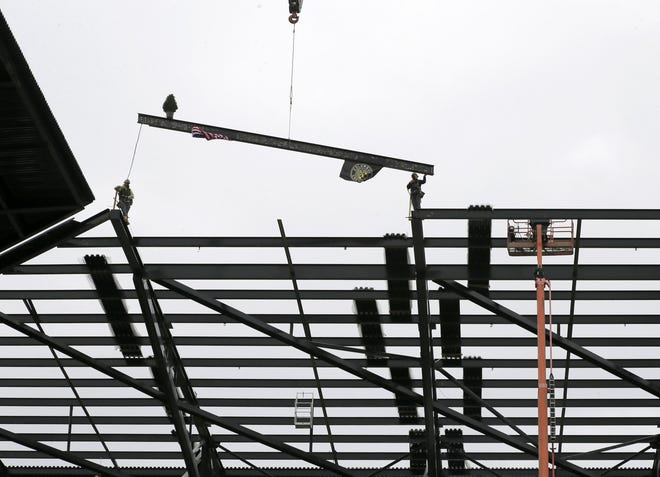 Construction workers place the final steel beam at the Crew's new Downtown stadium, which is set to open this summer.
