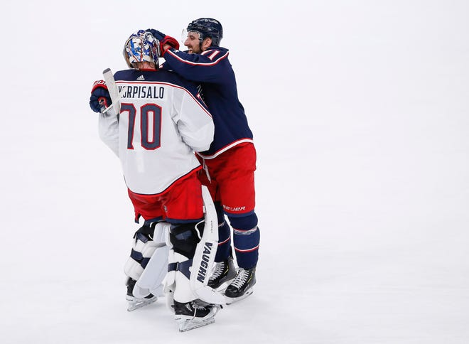 Blue Jackets left wing Nick Foligno (71) jokingly hugs goaltender Joonas Korpisalo (70) after scoring his third goal of the game late in the second period of the first scrimmage of training camp Wednesday night at Nationwide Arena.
