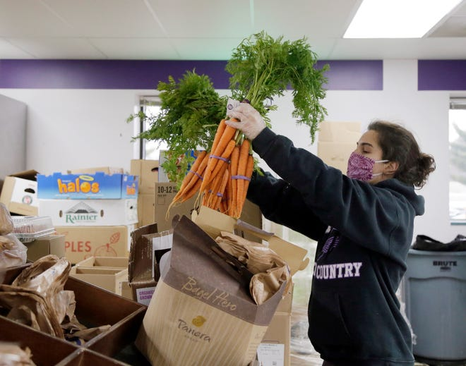 Volunteer Maria Vrcek unpacks bunches of carrots to be included in boxes of food inside the Saint Stephens Community House Food and Nutrition Center on the north side of Columbus, Oh. on Wednesday, January 6, 2021. The Saint Stephens Food and Nutrition Center will disperse 100 to 130 boxes of food during a shift, which includes non-perishable items as well as fresh fruits, vegetables and proteins. Baby items, toiletries and pet food is also available in limited quantities.