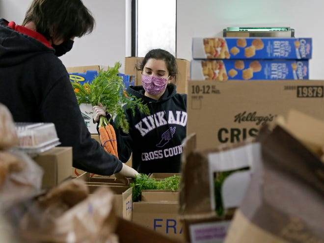 Volunteer Maria Vrcek unpacks bunches of carrots to be included in boxes of food inside the Saint Stephens Community House Food and Nutrition Center on the north side of Columbus. The Saint Stephens Food and Nutrition Center will disperse 100 to 130 boxes of food during a shift, which includes non-perishable items as well as fresh fruits, vegetables and proteins. Baby items, toiletries and pet food is also available in limited quantities.