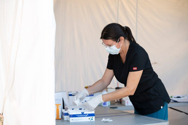 A health care worker prepares rapid tests for COVID-19 at the Lake Square Mall in Leesburg. [Cindy Peterson/Correspondent]