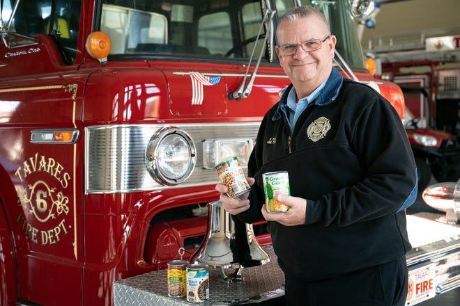 Tavares Fire Chief Richard Keith holds non-perishable food donations for the tri-city Fire Department food drive on Saturday. [Cindy Peterson/Correspondent]