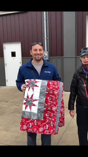OSU fan Ryan Ford holds the quilt he won in the Children's Dyslexia Center quilt raffle fundraiser.