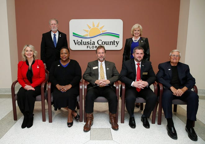 New and present Volusia County Council members standing Ben Johnson and Billie Wheeler, seated l to r, Heather Post, Barbara Girtman, Jeff Brower, Danny Robins and Dr.Fred Lowry pose for their official photo in DeLand, Thursday, Jan. 7, 2021.