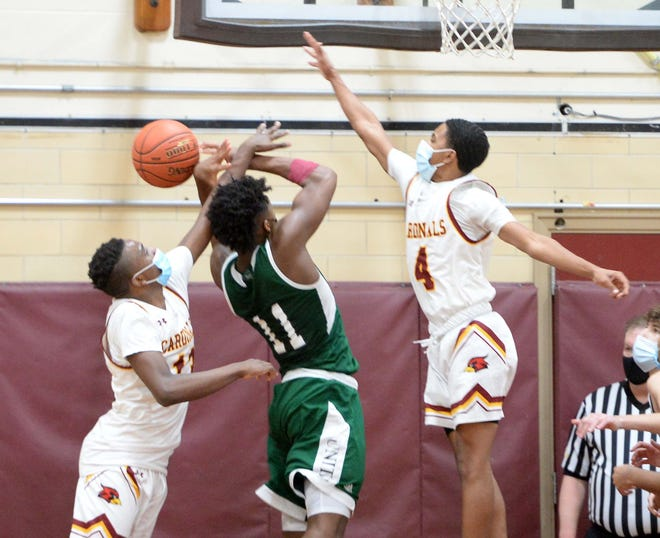 From left, Cardinal Spellman's Jaydan Exalus, was called for the foul on Austin Prep's Altenor, during their game, Wednesday, Jan. 6, 2021. Spellman's other defender was Calvin DePina.