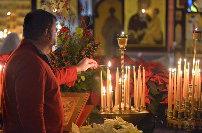Parishioner Neal Devlin lights candles during a Christmas Eve service at the Russian Orthodox Church of the Nativity on Wednesday.