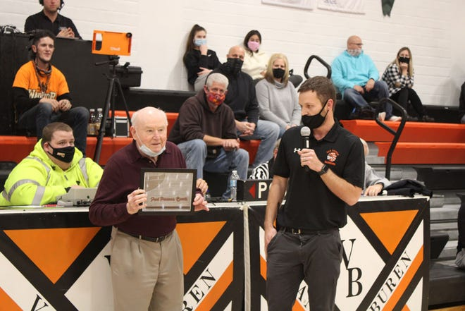 Van Buren County High School boys basketball coach Fred Parsons is honored by having the basketball court named in his honor during a ceremony Tuesday at Keosauqua. Van Buren County athletics director Wes McGraw (right) presents Parsons with a plaque.