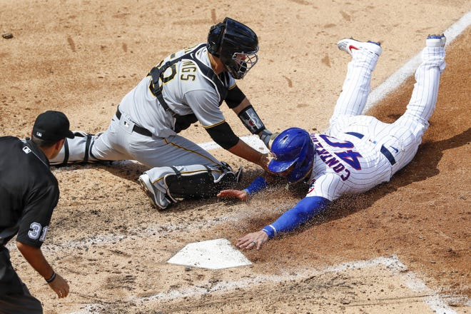 Cubs catcher Willson Contreras slides safely under the tag of Pirates catcher Jacob Stallings in the fifth inning in a game on Aug. 2, 2020, at Wrigley Field in Chicago.