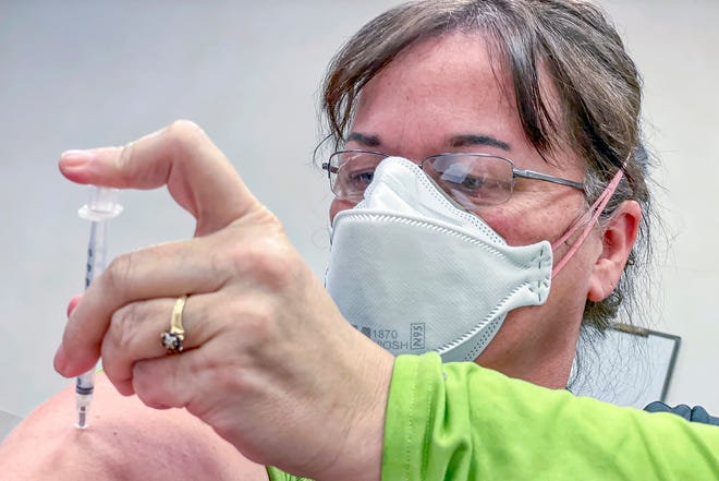 Cottage Hospital emergency room RN Anna Hedrick self-administers a dose of the Pfizer COVID-19 vaccine at the hospital on Wednesday, Jan. 6, 2021.