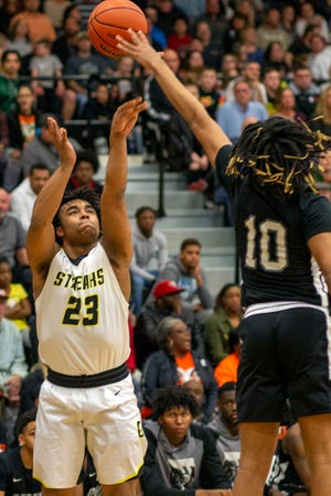 Galesburg's Eric Price puts up a shot over a Peoria Manual defender on Friday, March 6, 2020, in Class 3A regional championship action at Johh Thiel Gym.