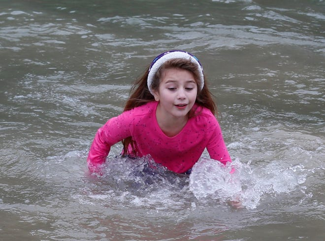 Sophia Degelia, 8, of Mesquite, scrambles to get out of the chilly water at the fifth annual Dino Dive at Dinosaur Valley State Park on New Year's Day. It was her first time to participate in the event.