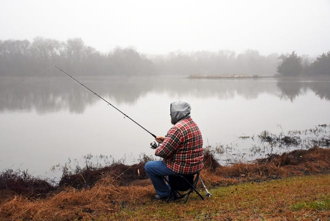 A man fishes at an area lake in 2019. Cold and wet weather may be in the in the forecast this weekend.