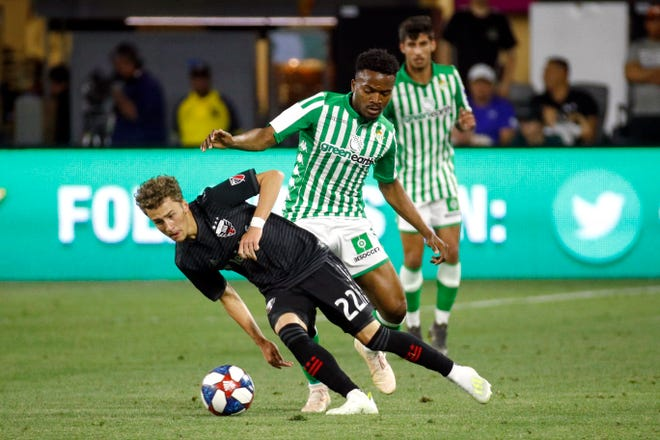 D.C. United forward Griffin Yow (22) tries to maintain possession as he is pressured by Real Betis midfielder Wilfrid Kaptoum during the second half of a friendly soccer match Wednesday, May 22, 2019, in Washington. Kaptoum will be playing for the N.E. Revolution in the upcoming season. (AP Photo/Patrick Semansky)